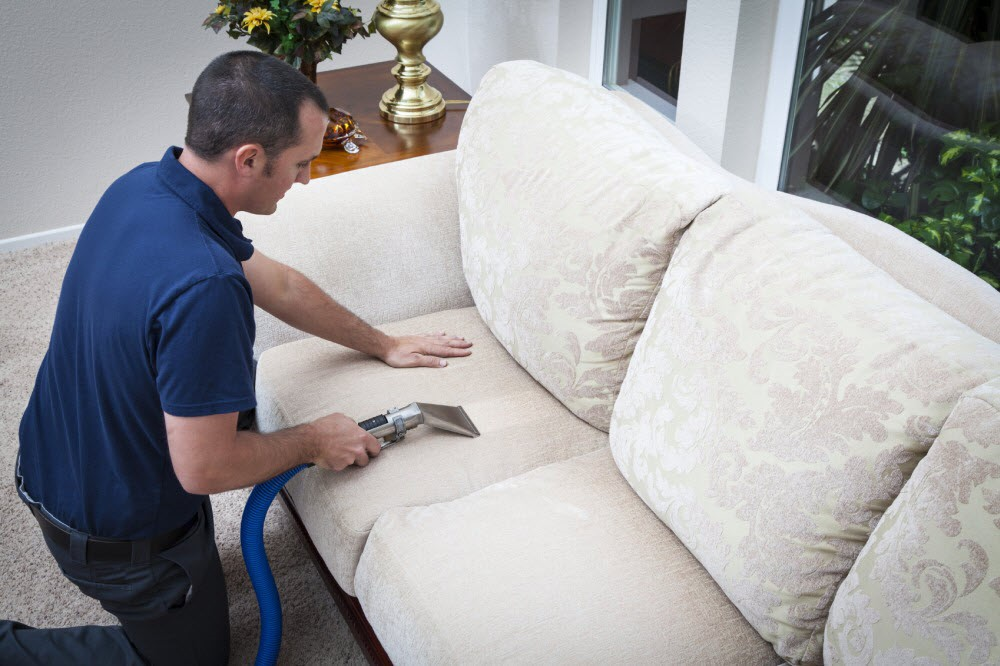 man cleaning sofa upholstery blount's complete home services fire water restoration termite pest control augusta ga